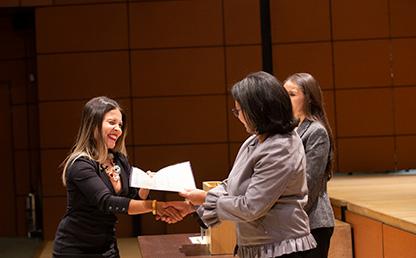 Foto de estudiante mujer que recibe diploma de posgrado en Uniandes