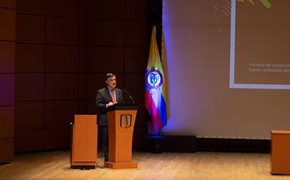 Foto en plano general de Carl Langebaek, vicerrector académico de Uniandes en atril ofreciendo discurso.