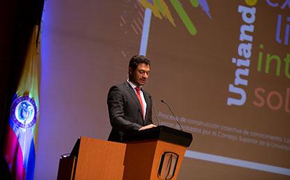 Vicerrector de Uniandes Eduardo Behrentz junto a bandera de Colombia, de pie, hablando a auditorio