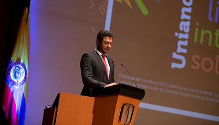 Vicerrector de Uniandes junto a bandera de Colombia, de pie, hablando a auditorio
