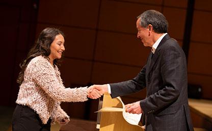 Mujer recibe diploma de grado por parte de directivo de Uniandes