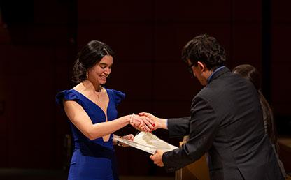 Mujer de vestido azul recibe diploma