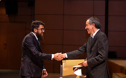 Hombre de barba recibiendo diploma y saludando a quien le hace entrega de su título.