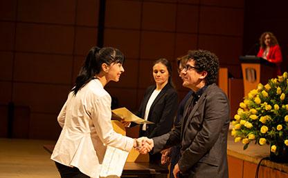 Mujer recibiendo diploma de grado de la Universidad de los Andes