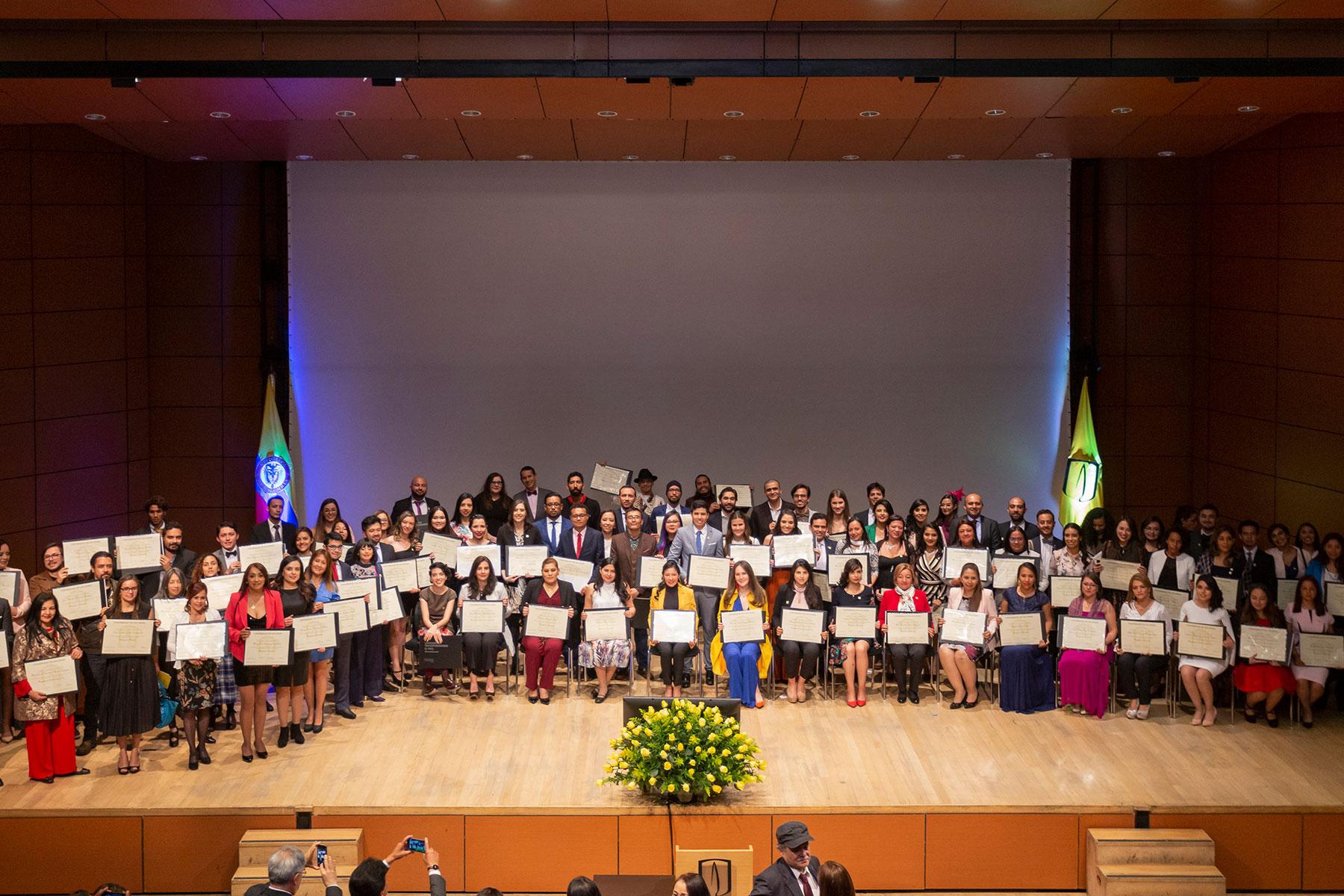 Graduandos ceremonia de posgrados posando en grupo para foto