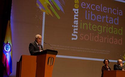 Luis Gonzalo Jaramillo Echeverry hablando frente a micrófonos en auditorio Uniandes, con imágen de fondo en donde se lee: excelencia, libertad, integridad y solidaridad