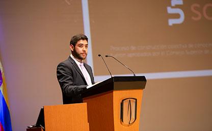 Graduando habla en micrófono en ceremonia de grados.