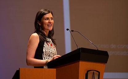 Foto de graduanda, Natalia Alexandra Gallego, ofreciendo discurso frente a atril con logo de Uniandes