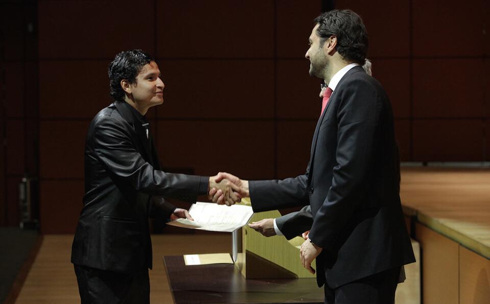 joven de traje negro brillante estecha la mano con otro hombre en señal de agradecimiento
