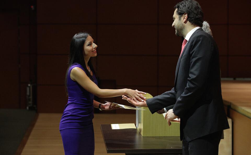 mujer de vestido azul y pelo largo estrecha la mano de un hombre alto