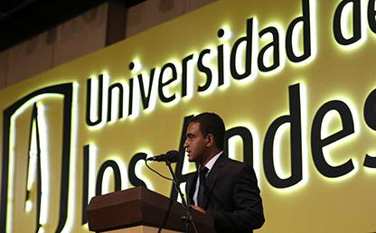 Fabián Vega frente a atril Uniandes dando discurso de grado