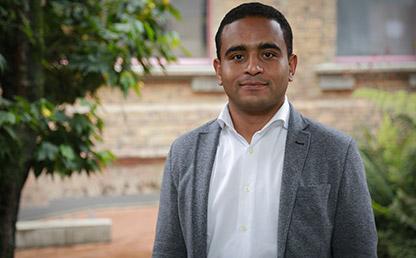 Daniel Fabián Vega, estudiante que recibió la distinción delante de un edificio de la Universidad de los Andes