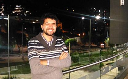 Miguel Ángel Ballesteros, estudiante que recibió la distinción recargado sobre una estructura de vidrio