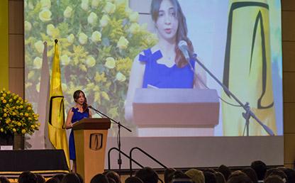 Daniela Fazio Vargas, Graduanda del Departamento de Historia Uniandes, fente a atril y proyectada en video de fondo mientras ofrece discurso de graduación.