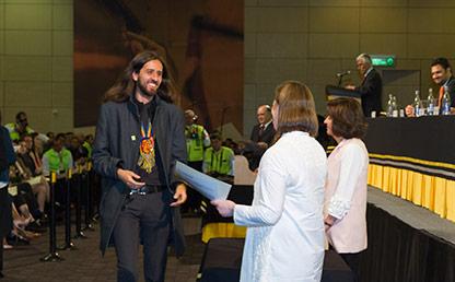 Graduando recibe diploma profesional en ceremonia de grado Uniandes
