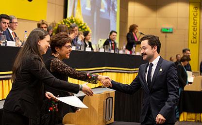 Graduando recibiendo su diploma por parte de dos mujeres en auditorio.