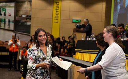 Mujer se acerca a profesora que le extiende su mano para entregarle diploma de grado