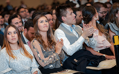 Foto plano abierto graduandos aplaudiendo durante la entrega de diplomas en ceremonia de grados 2019-2.