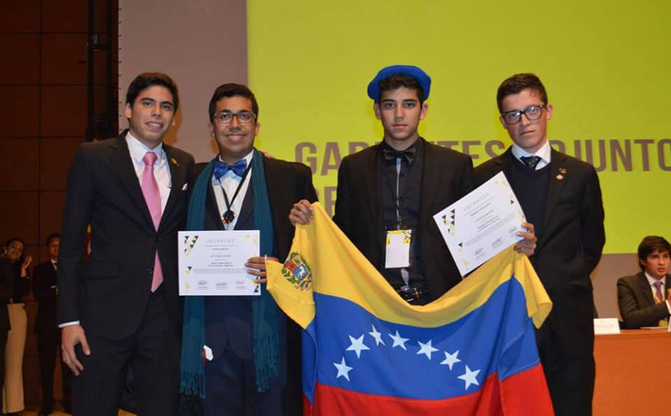 cuatro personas en un evento sostienen diplomas y una bandera de venezuela