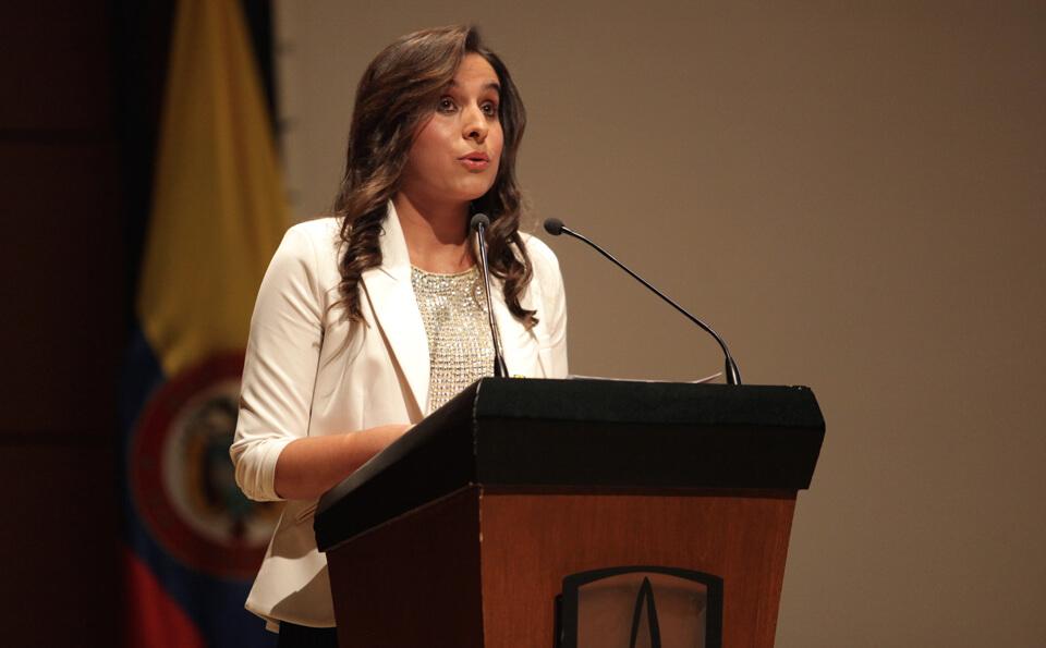 Una mujer de cabello largo y chaqueta blanca da un discurso en un atril