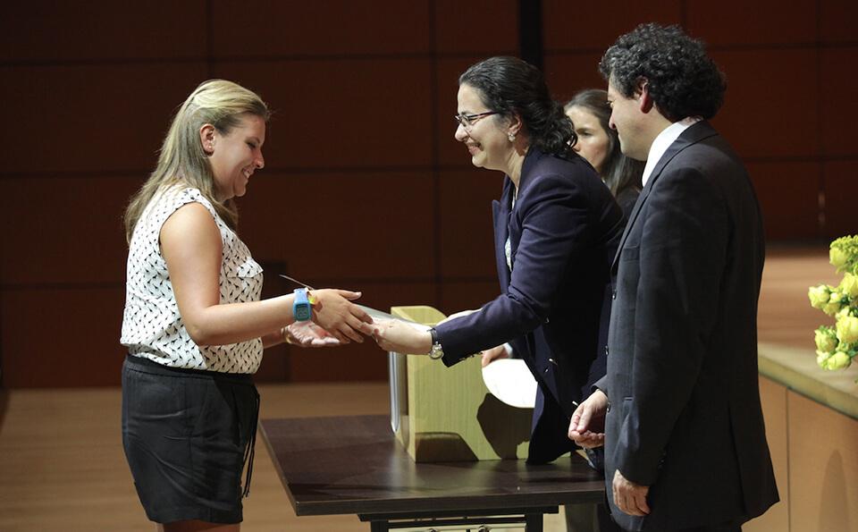 mujer de camisa blanca recibe diploma de manos de una mujer de chaqueta negra