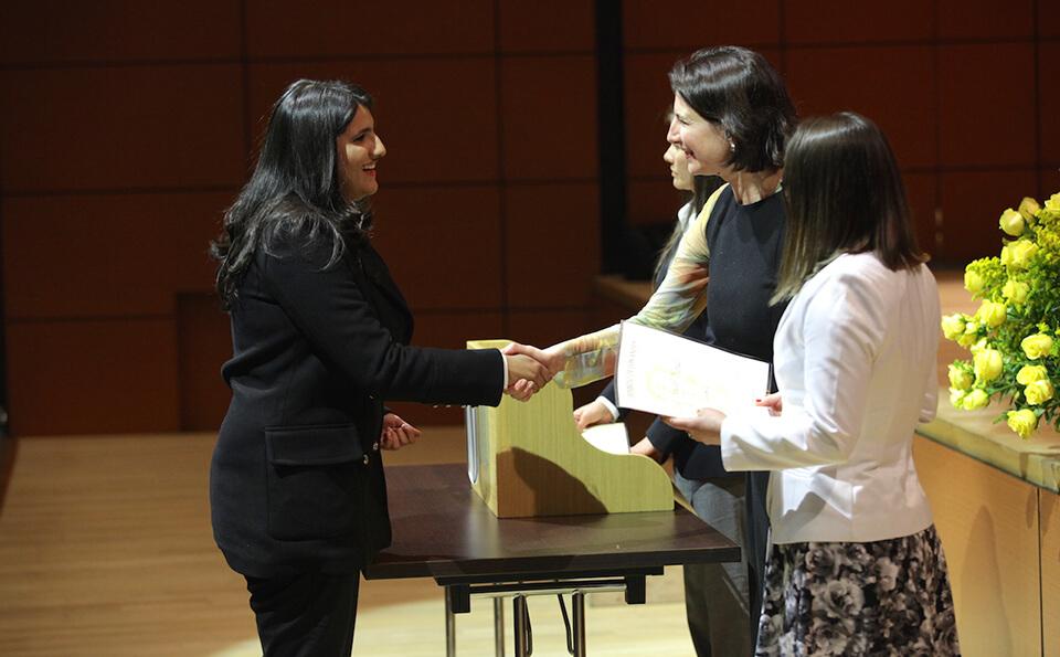 mujer de cabello negro y ropa negra recibe diploma de grado de otra mujer