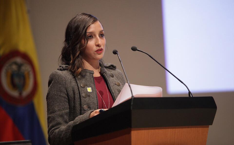 una joven de vestido vinotinto sostiene unas hojas en sus manos mientras da un discurso en un auditorio