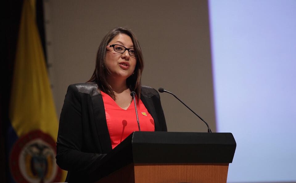 una mujer de vestido rojo, chaqueta negra y gafas da un discurso en una ceremonia