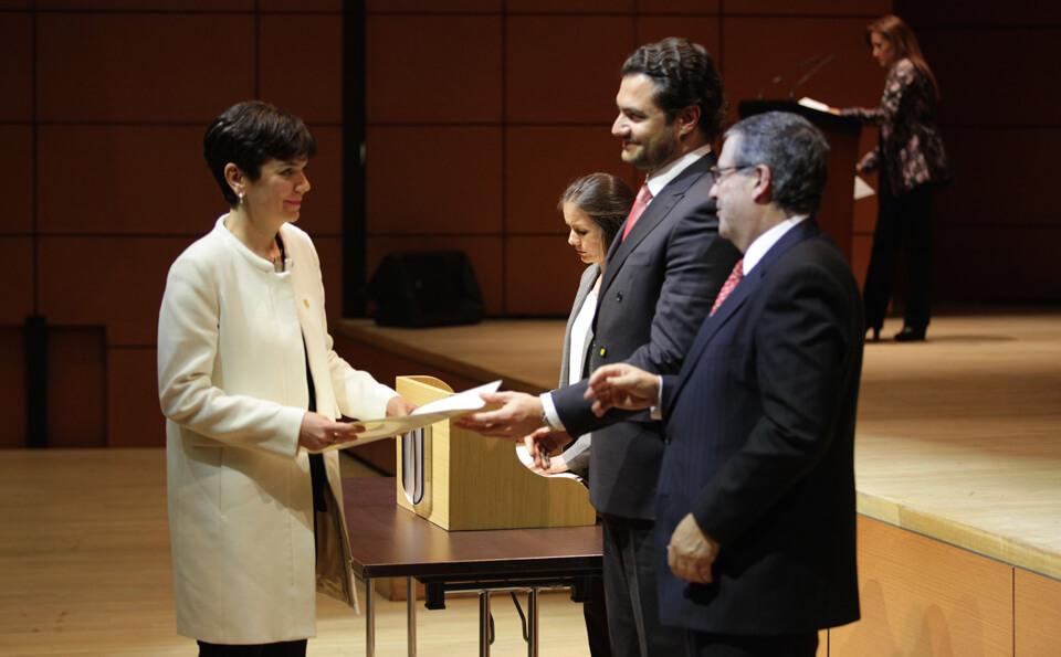 una mujer de vestido blanco recibe un diploma