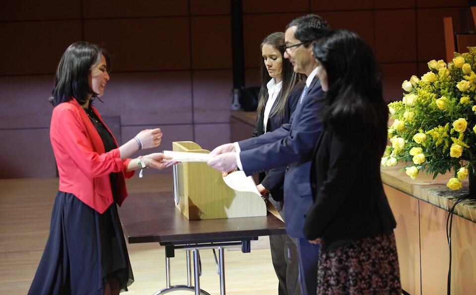 mujer de vestido negro y chaqueta roja recibe diploma de grado