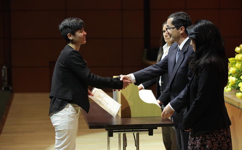 mujer de pantalon blanco recibe diploma de grado