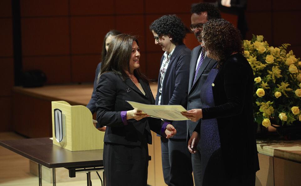 mujer de falda y chaqueta negra recibe diploma de grado