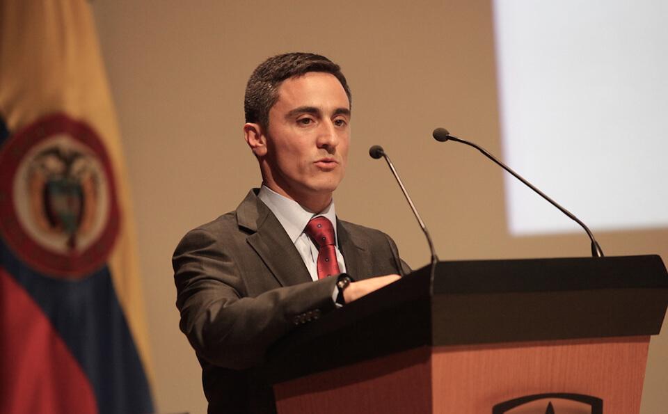 un hombre de traje gris con corbata roja está de pie junto a un atril dando un discurso