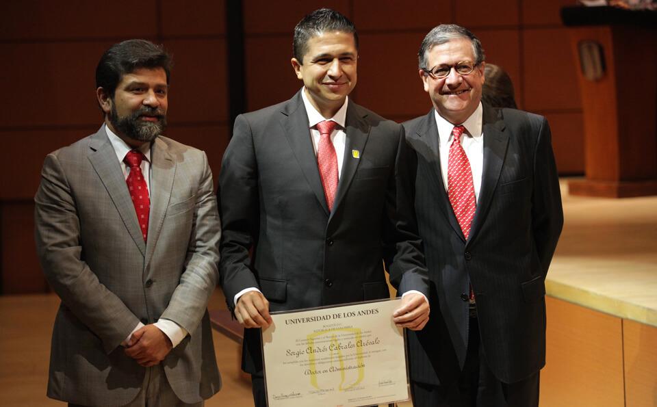 un hombre sostienen un diploma, lo acompañan dos hombres