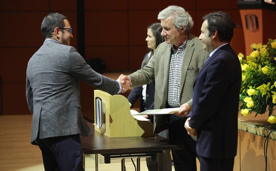 hombre de saco gris y gafas azules estrecha la mano de un hombre mayor vestido con camisa de cuadros