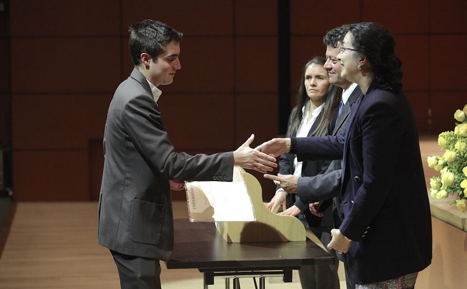 hombre de traje gris estrecha la mano con una mujer que le entrega diploma de grado