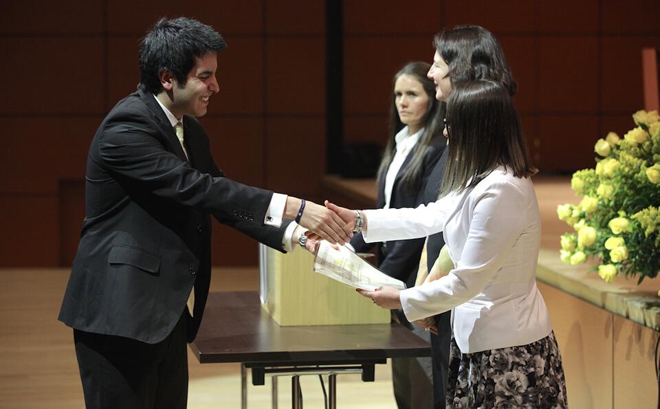 joven de traje negro estrecha la mano de una mujer de chaqueta blanca y le recibe diploma