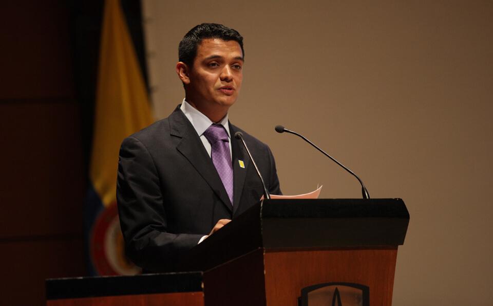 un hombre con traje y camisa lila da discurso en un evento