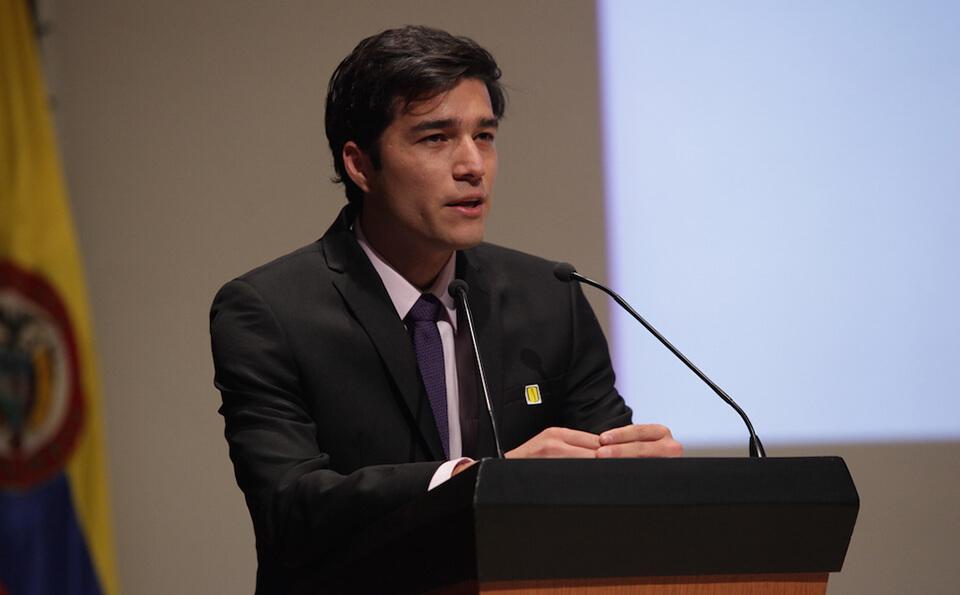un joven de traje negro y corbata azul está de pie junto a un atril dando un discurso
