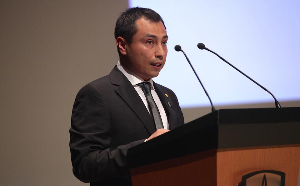un joven de traje negro y corbata negra está de pie junto a un atril dando un discurso