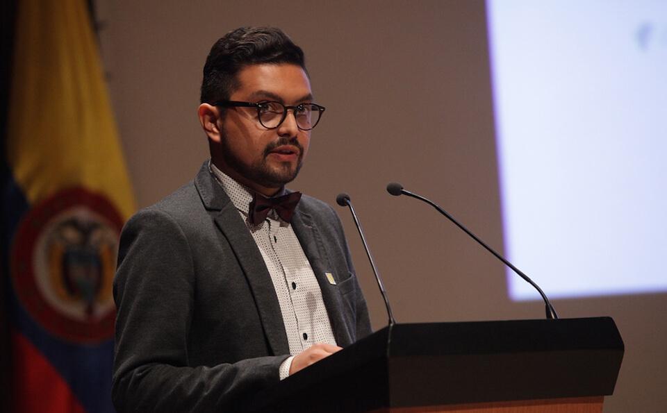 un joven de saco gris y corbatín está de pie frente a un atril dando un discurso en un auditorio