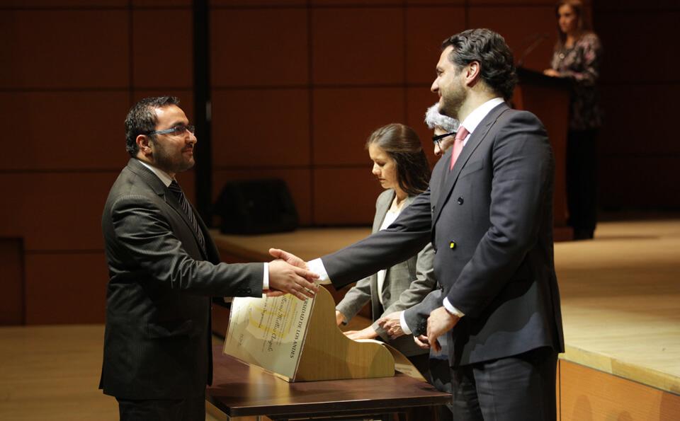 un hombre da la mano a otro hombre que recibe diploma de grado