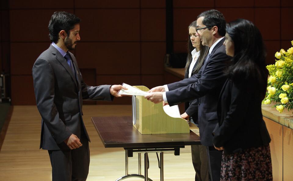 joven de corbata azul recibe diploma de grado en una mesa