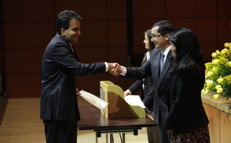 hombre alto estrecha la mano derecha con un hombre mayor, en su izquierda sostiene un diploma de grado