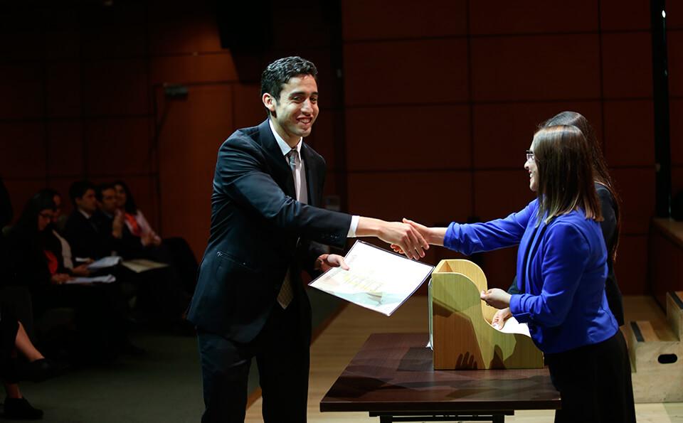 Foto graduando recibiendo diploma