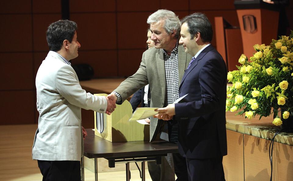 hombre de saco beige estrecha la mano de un hombre mayor y canoso al recibir diploma de grado