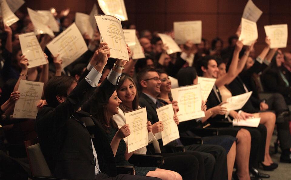 vemos a un grupo de personas en un auditorio, levantan sus diplomas en señal de celebración