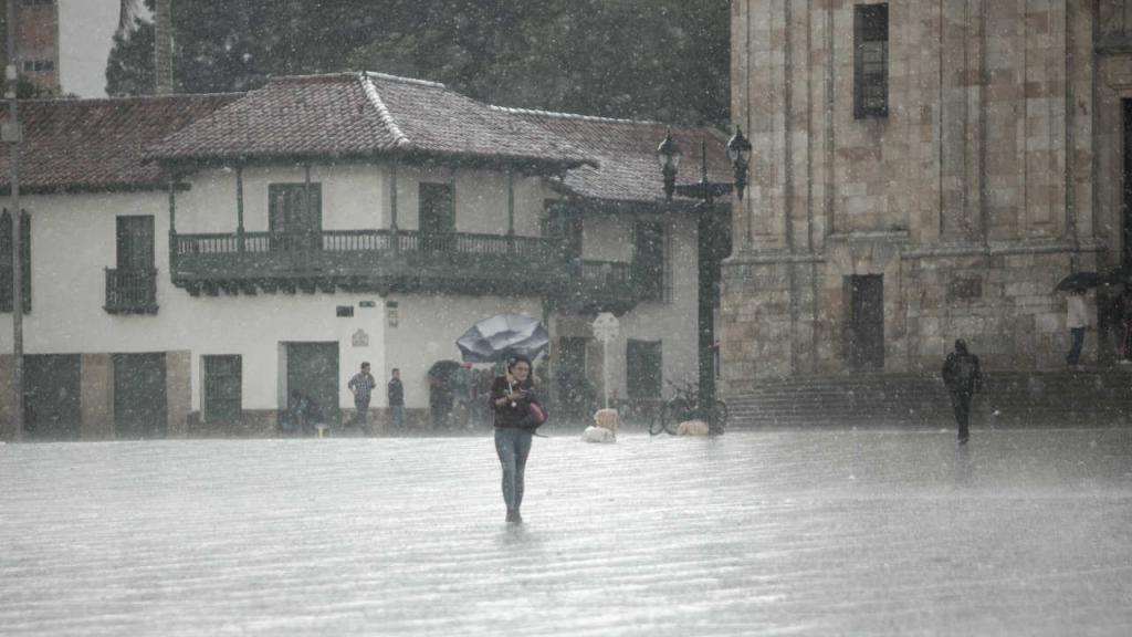 Una persona corriendo por aguacero con granizo en la Plaza de Bolívar.