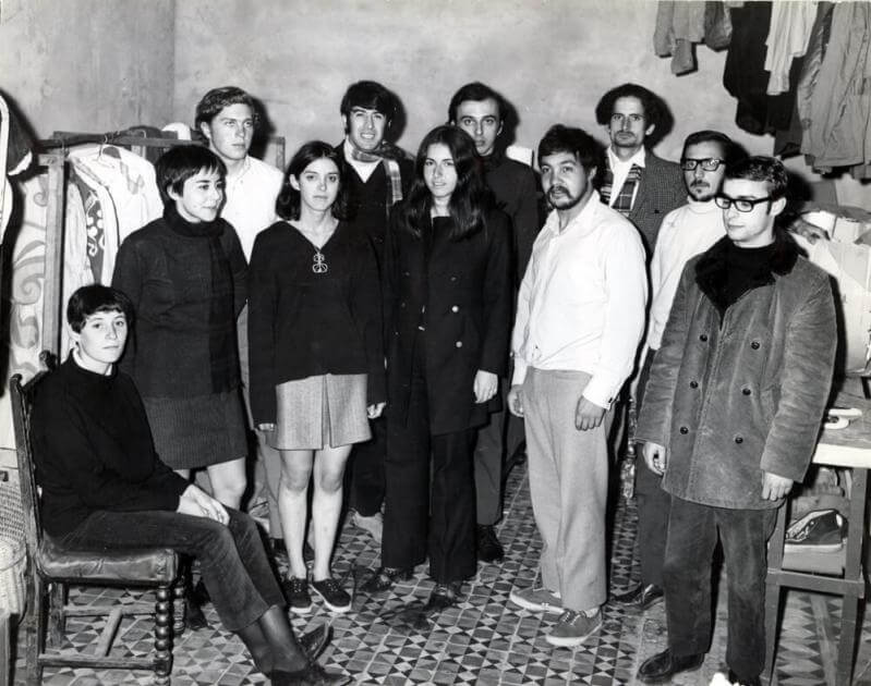 grupo de teatro de pie posando para la foto, hay hombres y mujeres. La foto es antigua y en blanco y negro