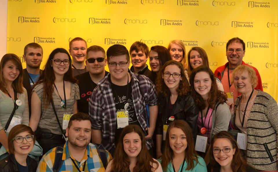 grupo de personas posando para la foto, el fondo es amarillo. Están participando en un evento